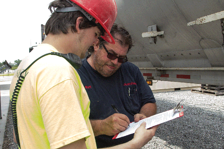 A feed mill employee gets the signature of an ingredient truck driver, which demonstrates safety of the product.