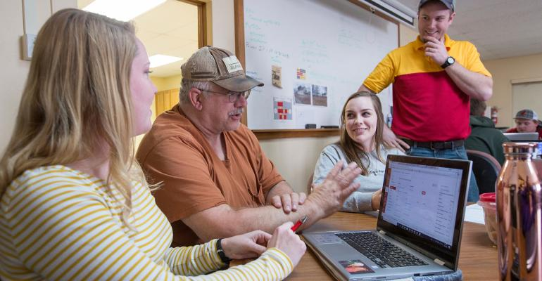Greg Vogel, Ag 450 farm operator, second from left, and Robby Frutchey, instructor-in-charge, standing, review operating budgets in the Ag 450 farm classroom with student farm managers Savanah Laur, left, and Marissa Lange.