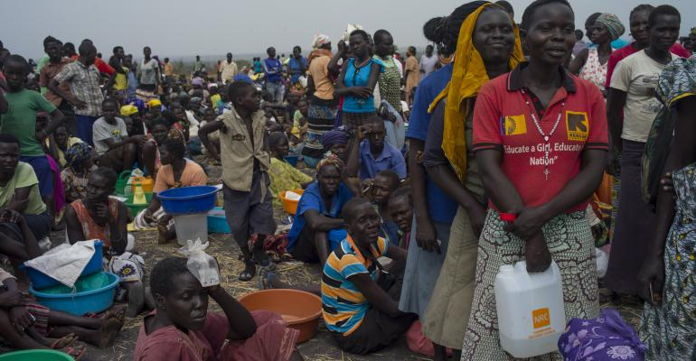 Refugees queue at a World Food Programme food distribution site at a refugee settlement