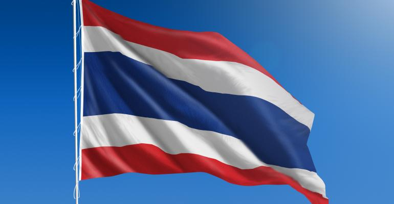 National flag of Thailand blowing in the wind in front of a clear blue sky