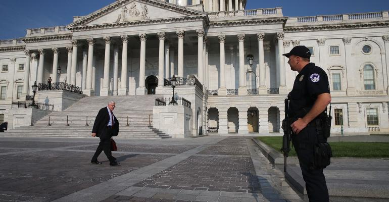 Sen. Michael Enzi (R-WY) walks past a U.S. Capitol Police officer standing guard in front of the U.S. Capitol Building, on June 14, 2017 in Washington, DC. This morning House Majority Whip Steve Scalise (R-LA) and others were shot by a gunman during Congressional baseball practice in Alexandria, Virginia.