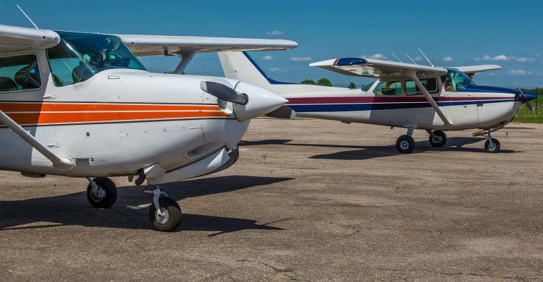 Two private light planes parked on the airfield in summer