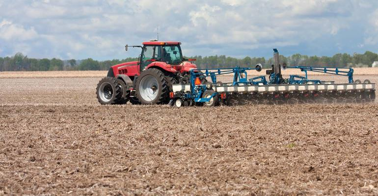Red tractor and blue planter planting corn.