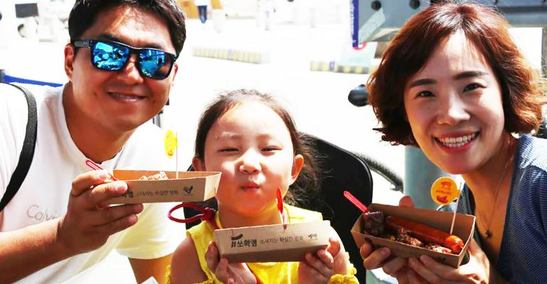"A Korean family enjoys U.S. pork sausages at ""Picnic on the Bridge"" in Seoul."