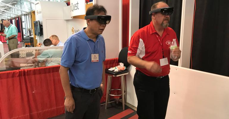 World Pork Expo visitors walk through a positive-pressure facility, which they're seeing in detail using augmented reality tools being pioneered by AP. The tech is just getting started at the company, but it offers interesting options for the future.