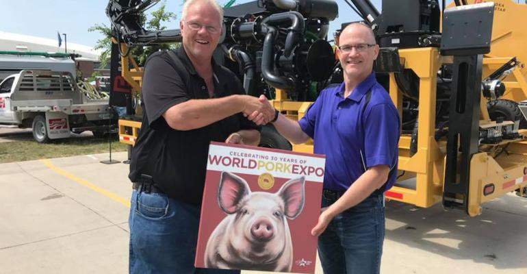 National Hog Farmer Staff Writer Kevin Schulz, right, presents a commemorative print to Steve Pittman, sales manager for Bazooka FarmStar, honoring the Full Throttle Outlaw being awarded the Producers' Choice award by World Pork Expo attendees.