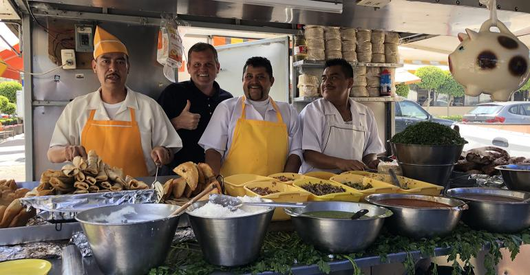 Craig Morris, National Pork Board Vice President of International Marketing, with three workers at a  a traditional food stand where they are making pork street food in Mexico City.