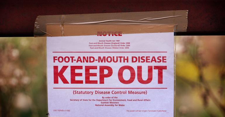 Keep out sign on gate warning of foot-and-mouth disease