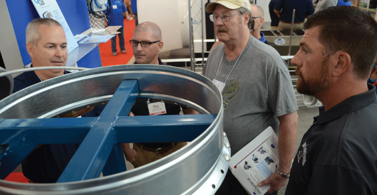 Hog Slat Sales Director Fritz Richards (far left) explains to New Product Tour judges (left to right) Brad Leuwerke, Gary Anderson and Pat Thome how the Poly Feed Bin Lid can be retrofitted to most existing feed bins.