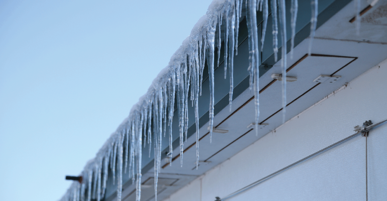 icicles hanging from the eave of a hog barn