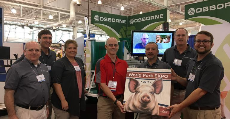National Hog Farmer Staff Writer Kevin Schulz (red shirt) presents the Osborne team with a commemorative print from the 2017 World Pork Expo, honoring them as this year's recipient of the Producers' Choice award.