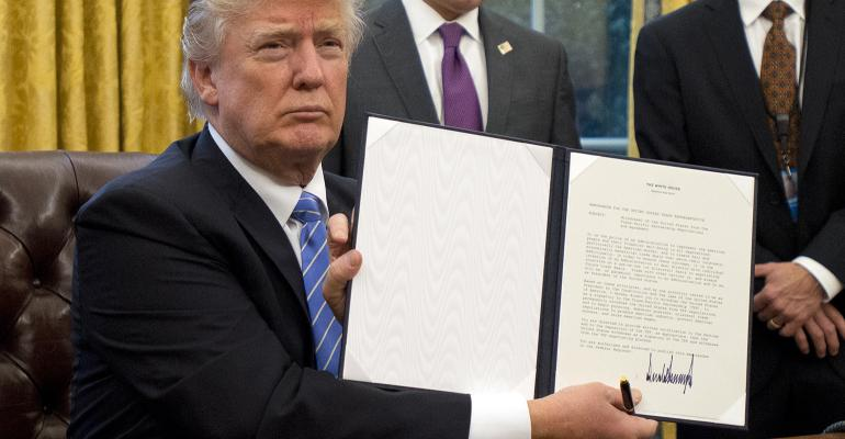 U.S. President Donald Trump shows the Executive Order withdrawing the United States from the Trans-Pacific Partnership after signing it in the Oval Office of the White House on Jan. 23.