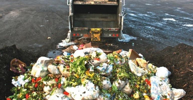 garbage truck dumping food waste in a landfill