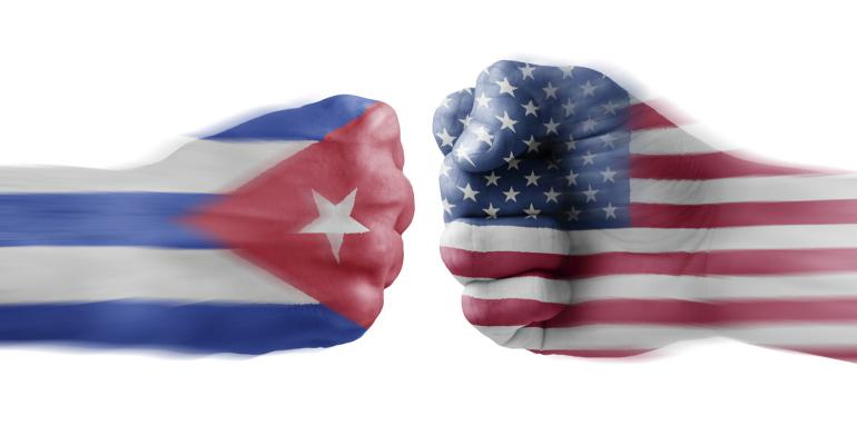 Two fists, one with a Cuba flag and one with U.S. flag