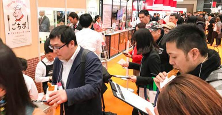 Visitors to FoodEx sample US. Beef and pork items at the USMEF booth inside the USA Pavilion.