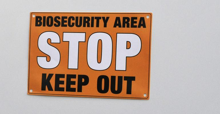 """Sign on a hog facility declaring """"Biosecurity Area: Stop. Keep Out"""""""