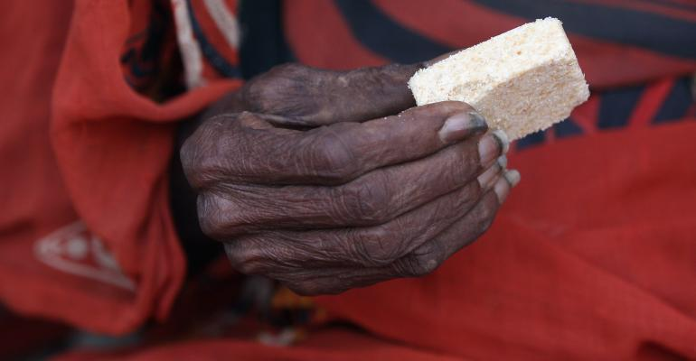 Elderly Somali refugee woman holds a high-energy biscuit ration