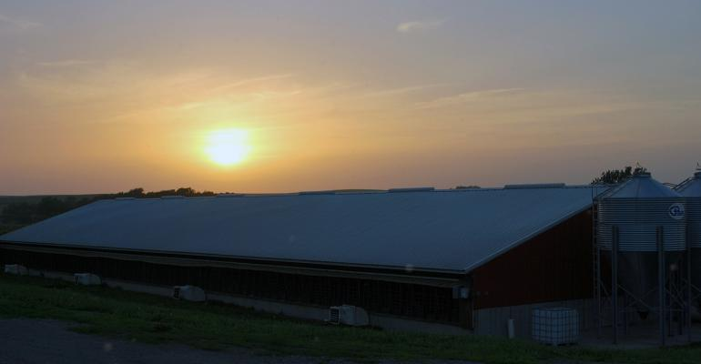 The sun sets over a red hog barn.