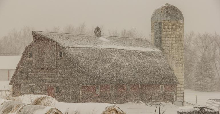 old barn and silo in a blizzard
