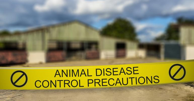 Animal disease control precautions tape in front of a barn
