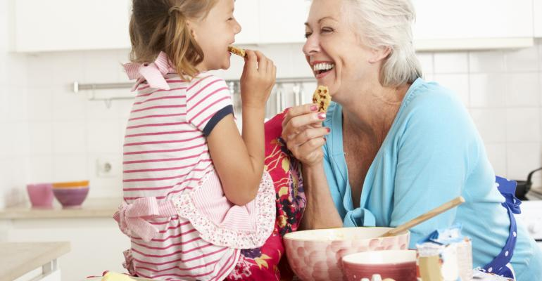 Grandmother And Granddaughter Baking In Kitchen Smiling And Laughing At Each Other.