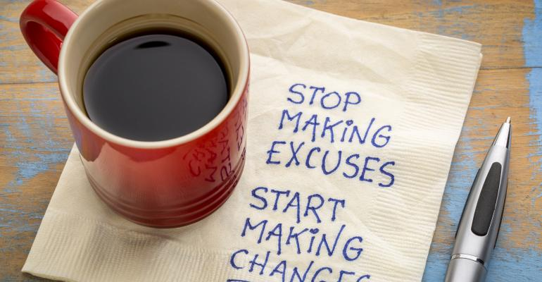 Stop making excuses, start making changes - handwriting on a napkin with a cup of coffee