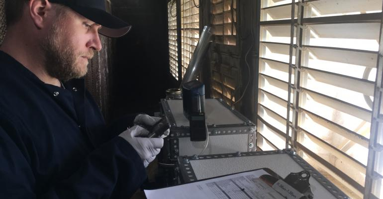 Devin Maurer tests the pilot scale UV treatment of swine barn air.