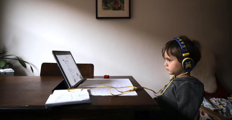 Child sitting in front of a computer for distant learning