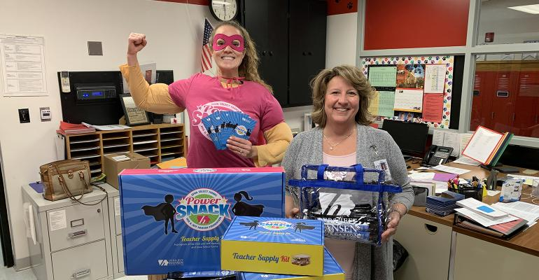 Allyson Ladd with Iowa Select Farms and the Deb and Jeff Hansen Foundation delivers PowerSnack Teacher kits to Alden South Side Elementary Secretary, Jodi Wohlford. Power Snack Teacher Kits contain pork sticks and four Power Snack booklets for each child.