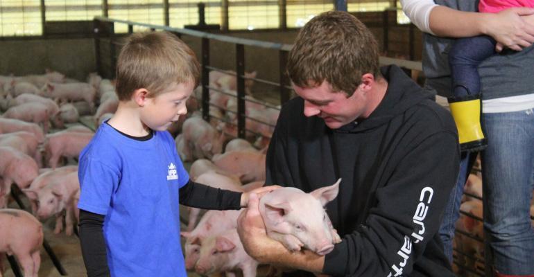nhf-npb-pig farmer-son-nursery pig-.jpg