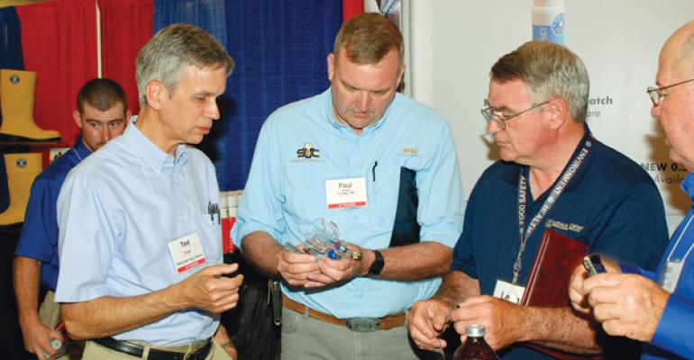 Paul Yeske center checks over the Prima Tech Vaccinator while World Pork Expo New Product Review Panelists Ted Funk left and leon Sheets right look on