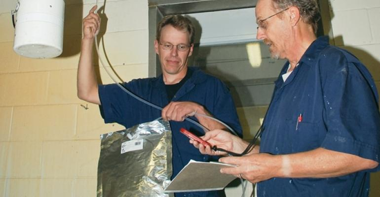 Agricultural engineers Brian Hetchler left and Larry Jacobson collected air samples in Flexfoil bags to measure common gas levels