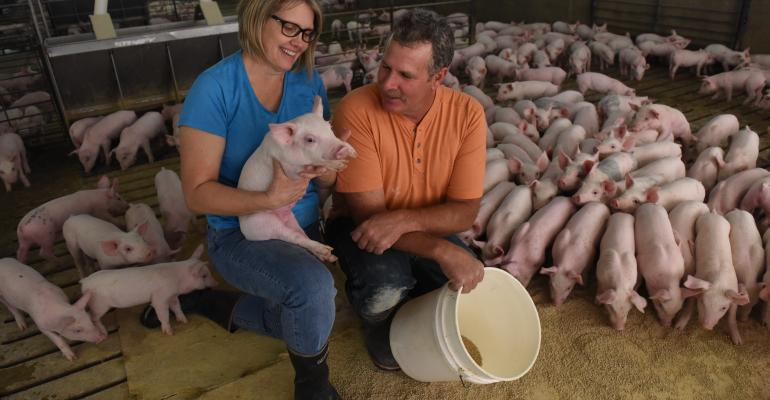 National Pork Boardrsquos 2016 Americarsquos Pig Farmer of the Year Brad Greenway and his wife Peggy feed pigs in one of their weantofinish pig barns on their farm near Mitchell SD