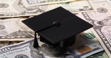 graduation cap on pile of money