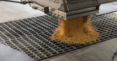 Corn is unloaded into the receiving pit after the pit cover has been removed. Jones says care should be taken to prevent corn being unloaded from accumulating past the grates to minimize contamination.
