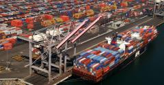Birds-eye view of a shipping yard with a freighter full of shipping containers.