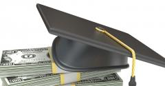 Graduation cap on stack of dollar bills.