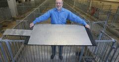 Robert Stwalley, assistant professor in the Department of Agricultural & Biological Engineering at Purdue University, shows a cooling pad designed to keep sows more comfortable during farrowing. The pads, developed by Stwalley and Allan Schinckel, professor in the Department of Animal Sciences, consist of 2-foot-by-4-foot aluminum tread plate on top of copper pipes that circulate water