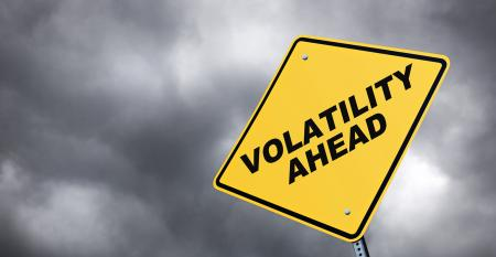 """Volatility ahead"" road sign with storm clouds in the background"