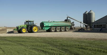 Tractor pulling a manure tank that is being filled with hog manure